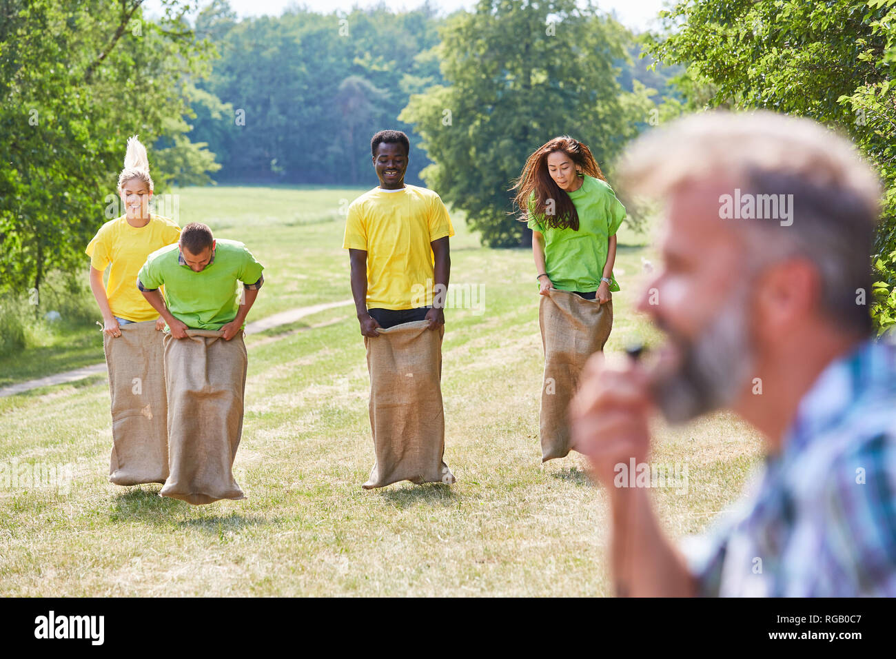 Group during sack race competition as a teambuilding event in summer - Stock Image