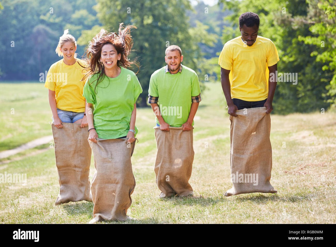 Teams play against each other Sack-hopping as a team building Event in the park - Stock Image