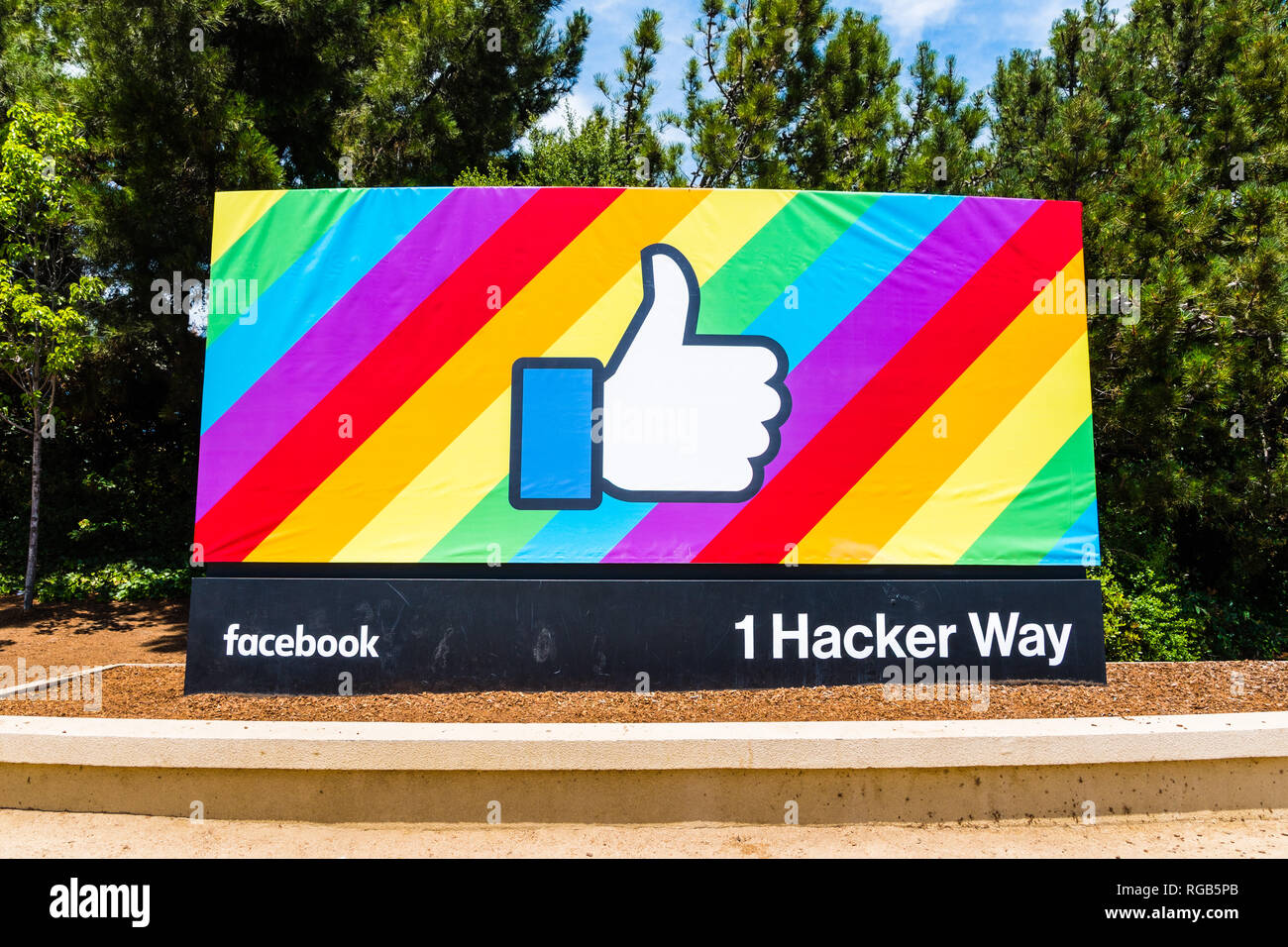 June 18, 2018 Menlo Park / CA / USA - The Facebook Like Button on a rainbow flag background, celebrating LGBTQ pride month; entrance to the company's  - Stock Image