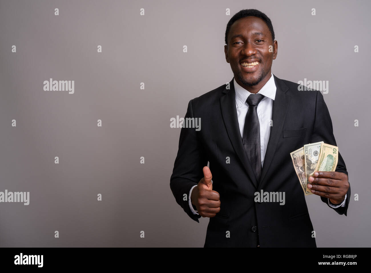 Young handsome African businessman holding money and smiling Stock Photo
