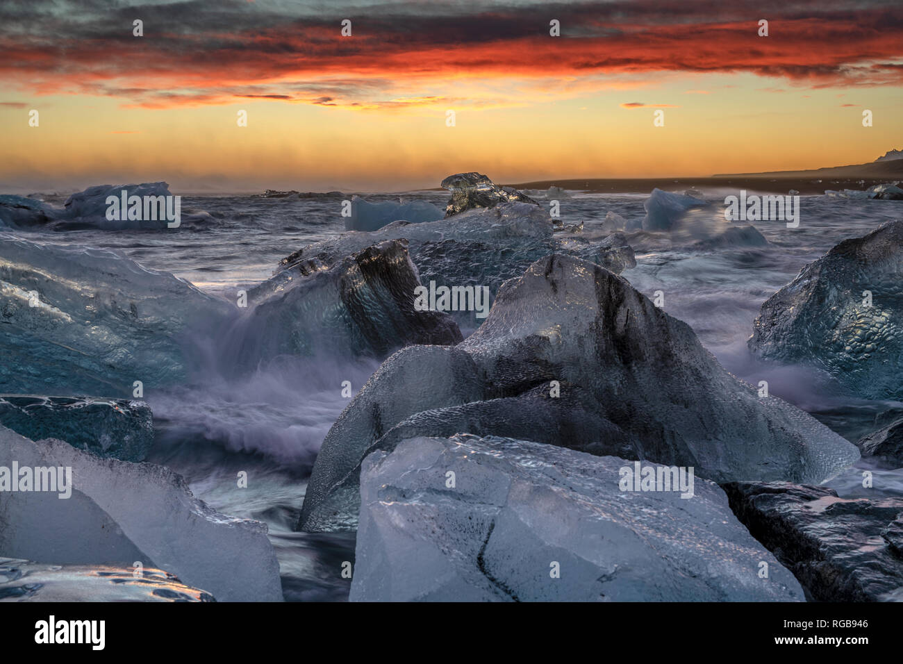 Raging heavy sea and winter storm makes large splashes and large waves on the huge ice blocks at the shore of North Atlantic Ocean at the famous glaci Stock Photo