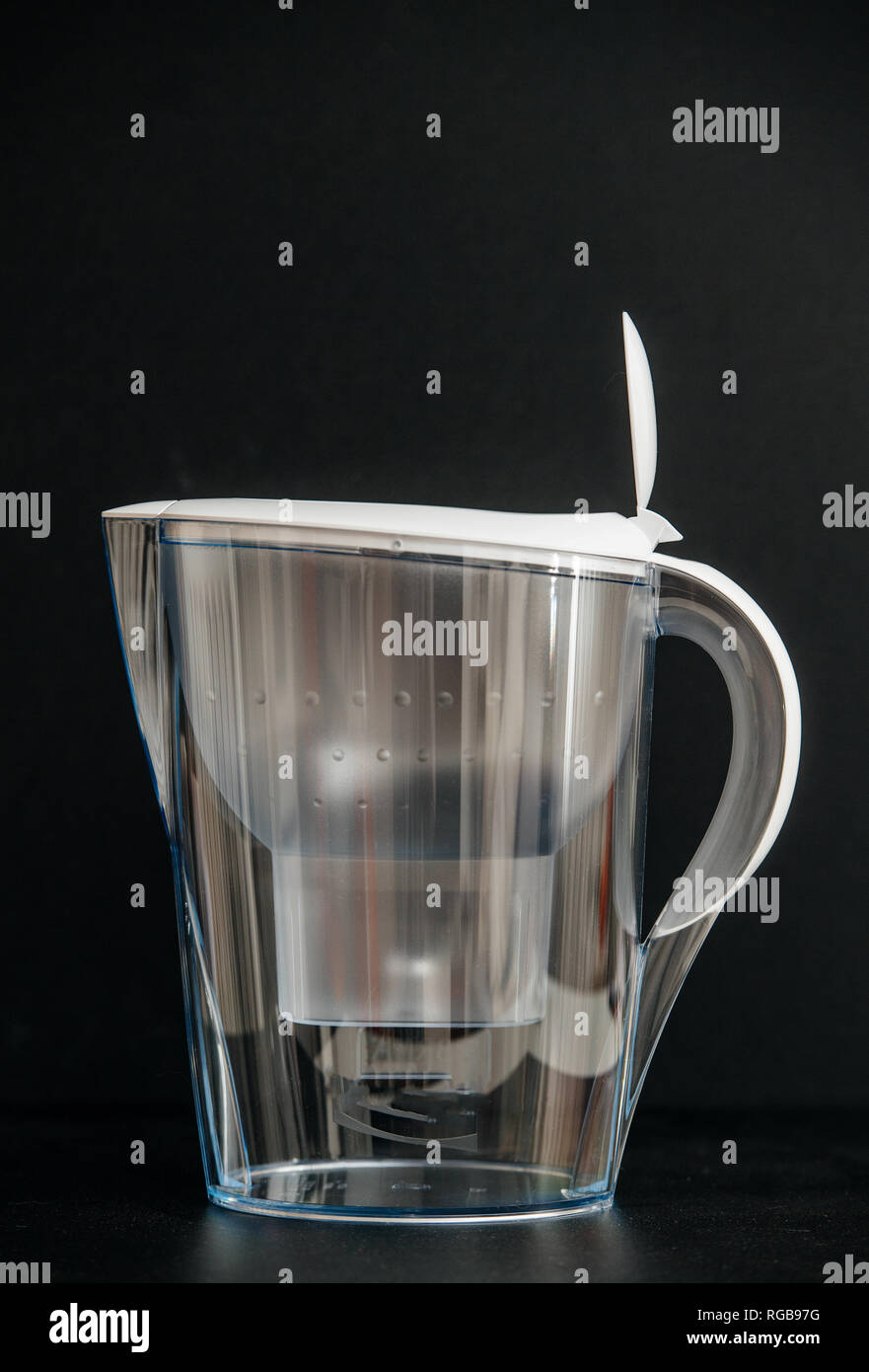 New water filter with opened plastic lid against black background - Stock Image