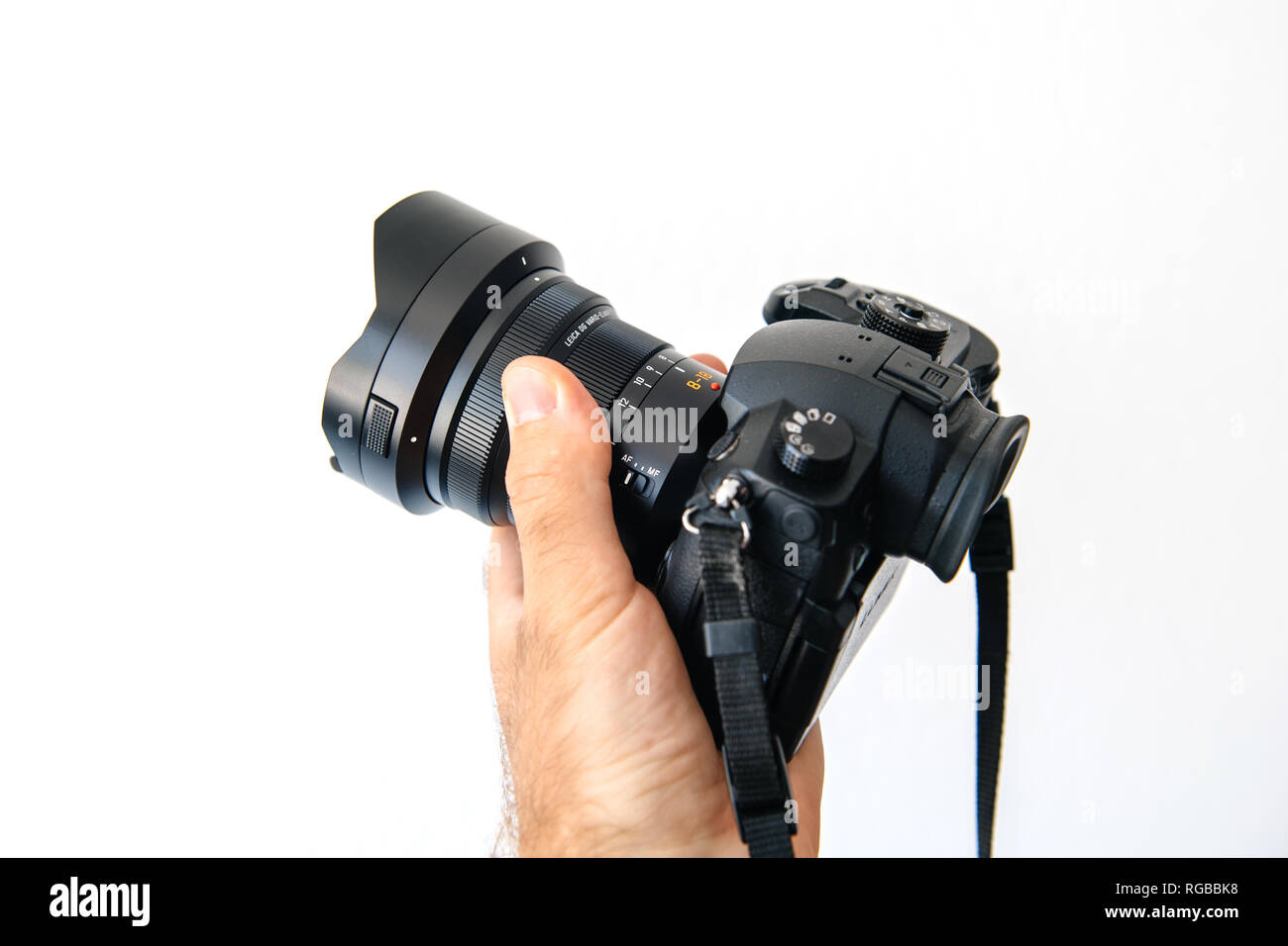 PARIS, FRANCE - JUN 30, 2018: Man showing new Panasonic Lumix DMC-GH5 - and newest Leica Vario-Elmarit 8-18 Micro Four Thirds System digital still and video camera with 4K 10 bit Video recording internal capability - Stock Image