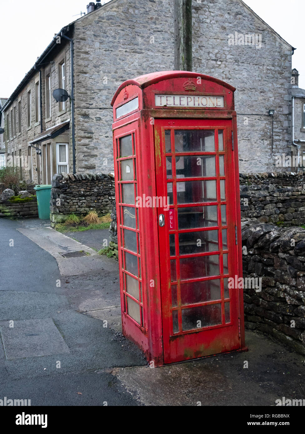 An old red telephone box in the village of Horton in Ribblesdale in the Yorkshire Dales. Stock Photo