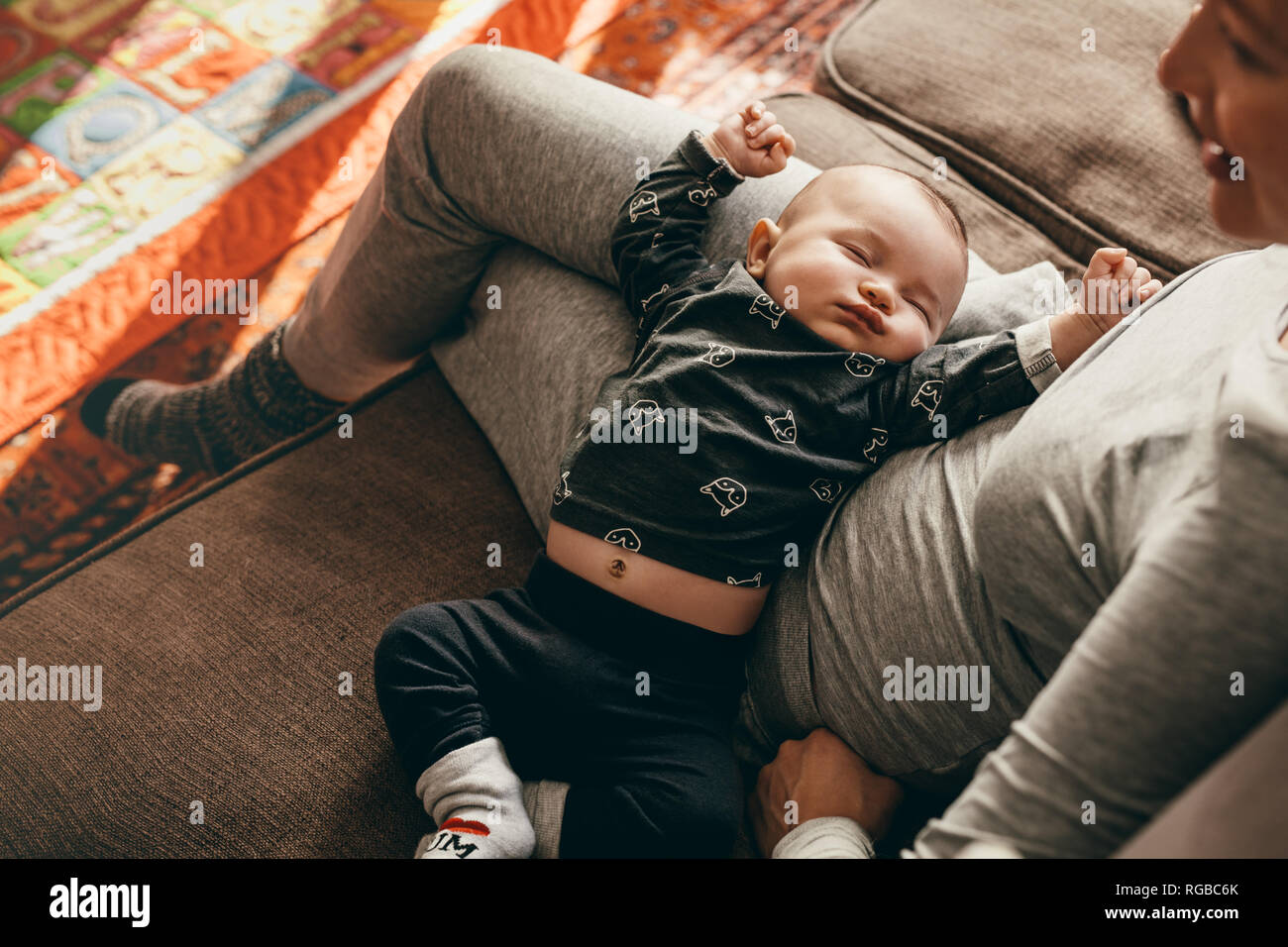 Baby in a deep sleep in the lap of his mother at home. Mother sitting on couch with her baby sleeping in her lap. - Stock Image