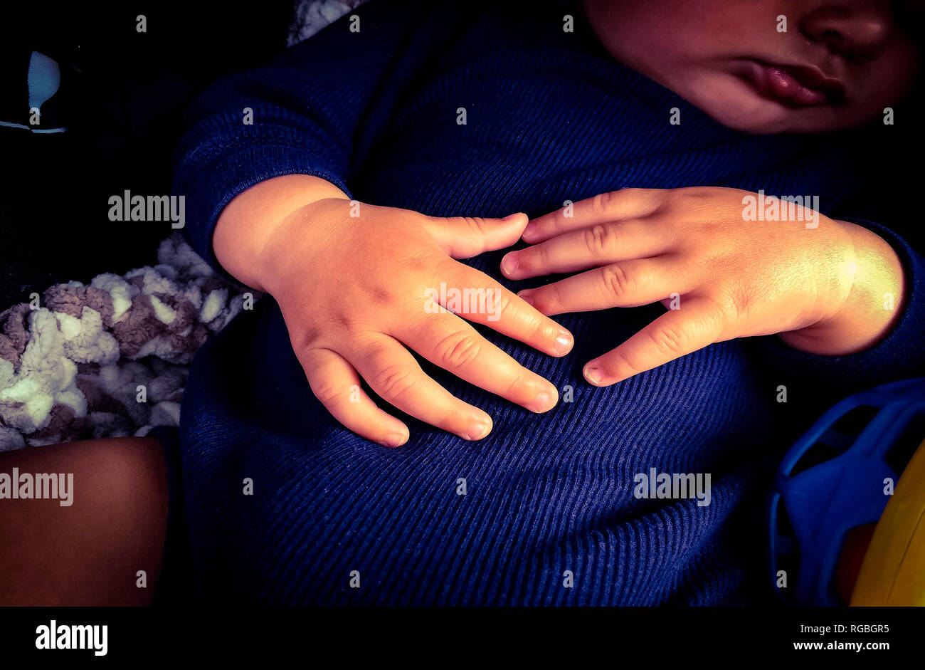 A toddler's relaxed hands indicate deep sleep and contentment, Nova Scotia, Canada - Stock Image