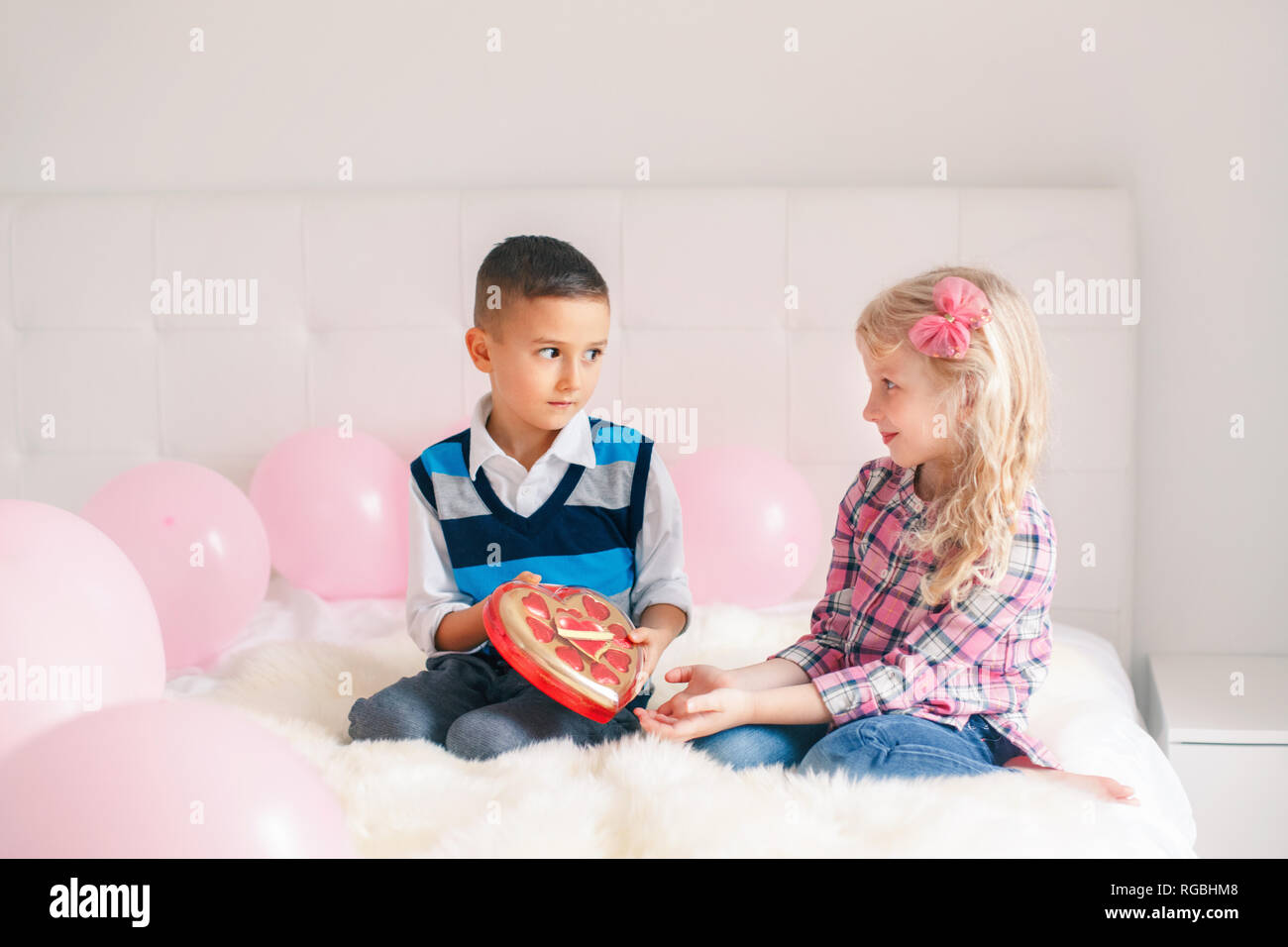 086deb31cdff8 Group portrait of two Caucasian cute adorable children eating heart shaped  candies. Boy giving girl