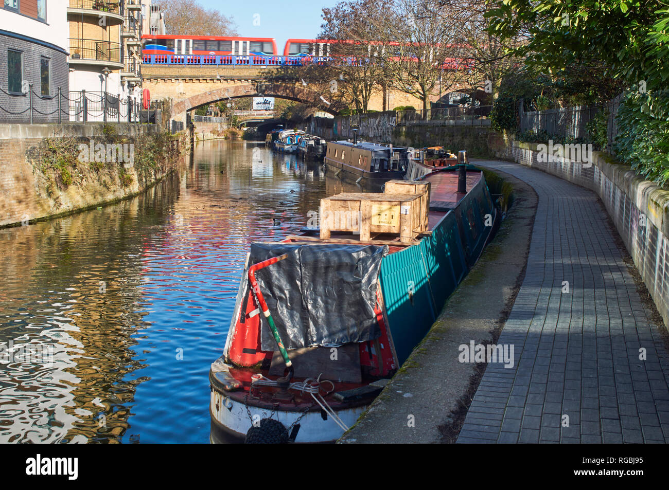 Limehouse Cut, Limehouse, East London UK, with narrowboats and the Docklands Light Railway crossing in background - Stock Image