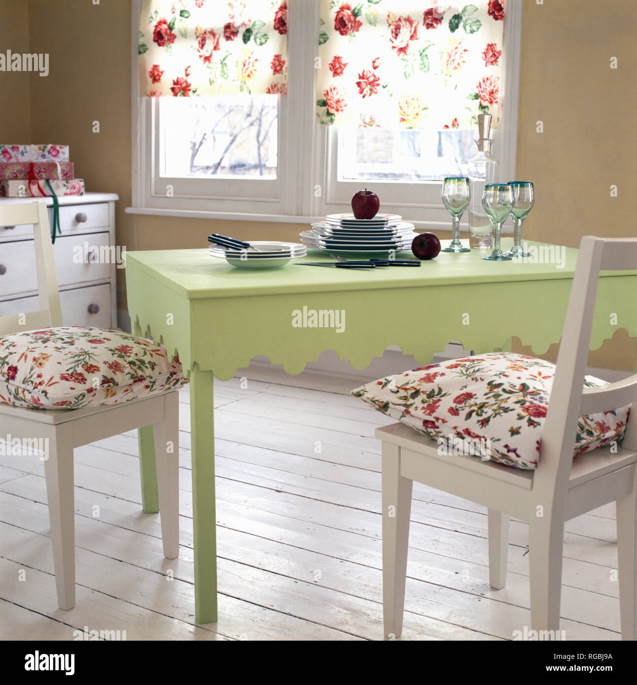 Floral cushions on white chairs at green painted dining ...