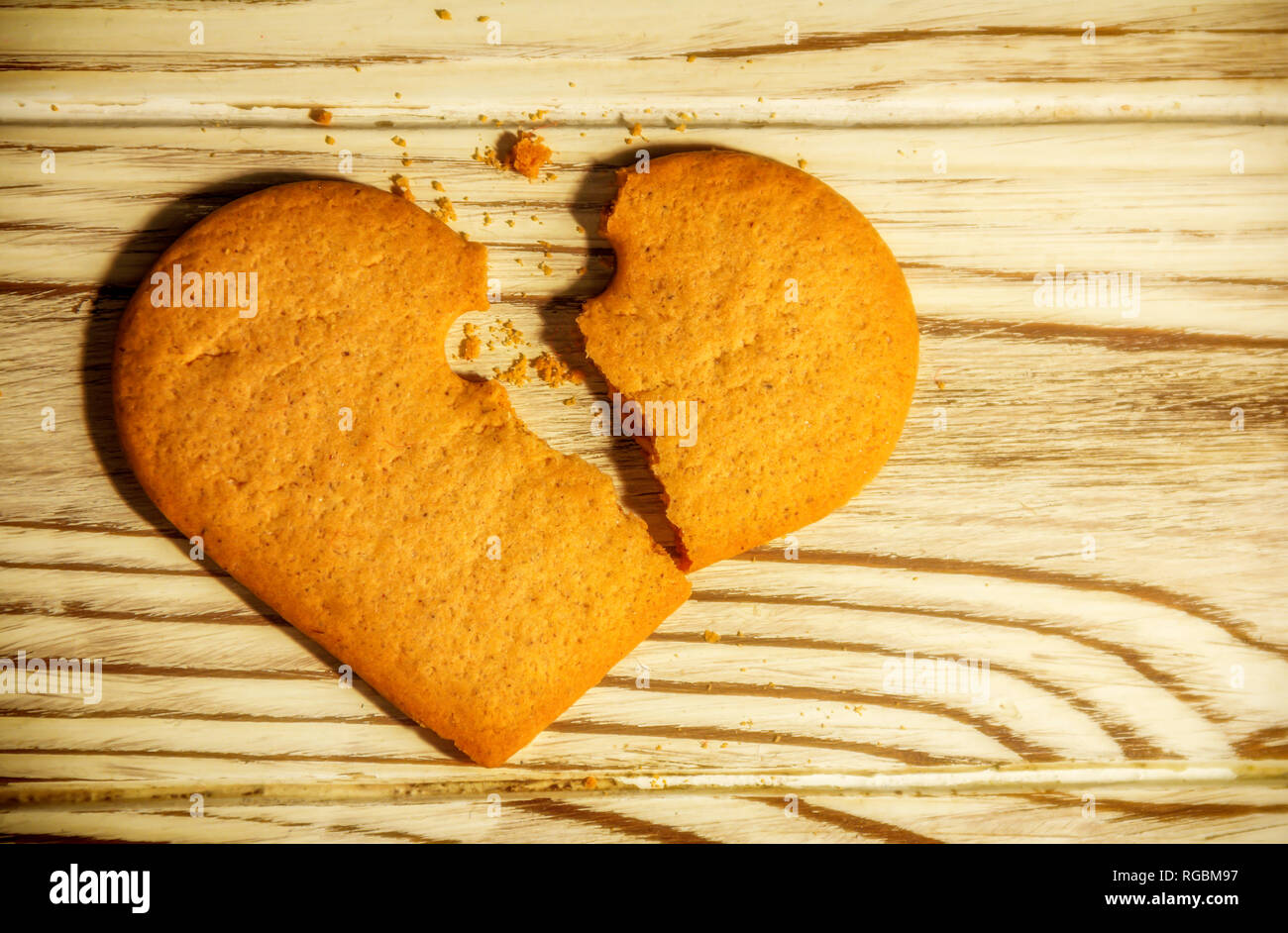 Broken Heart shaped ginger Cookies And Crumbs over wooden background, love concept - Stock Image