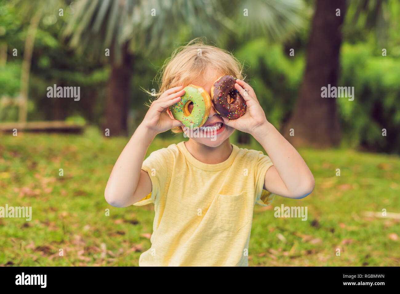 Funny boy with donut. child is having fun with doughnut. Tasty food for kids. Happy time outdoor with sweet food - Stock Image