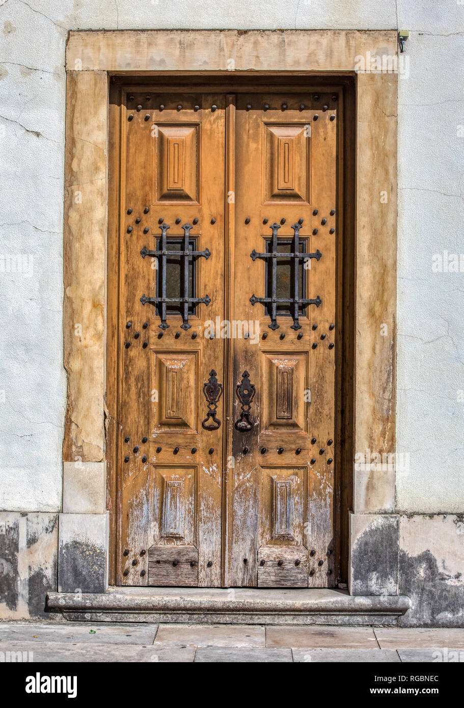 Photograph of a faded brown wood weathered castle door of medieval Portugal. Door has aged, rusted wrought iron bolts and fasteners. - Stock Image