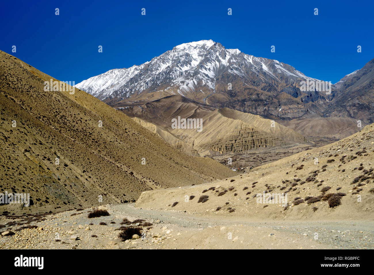 Dirt track leading to the village of Ghemi, partly visible in the distance. Upper Mustang region, Nepal. Stock Photo
