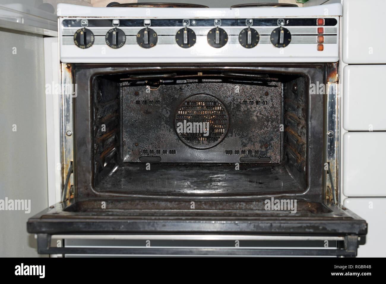 Very dirty oven, door open. - Stock Image