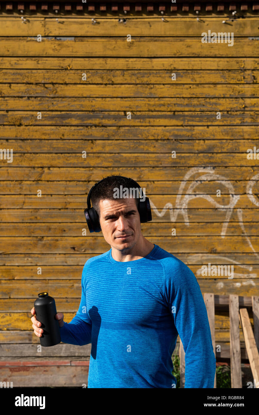 Athlete in front of wooden house with headphones and drinking bottle - Stock Image