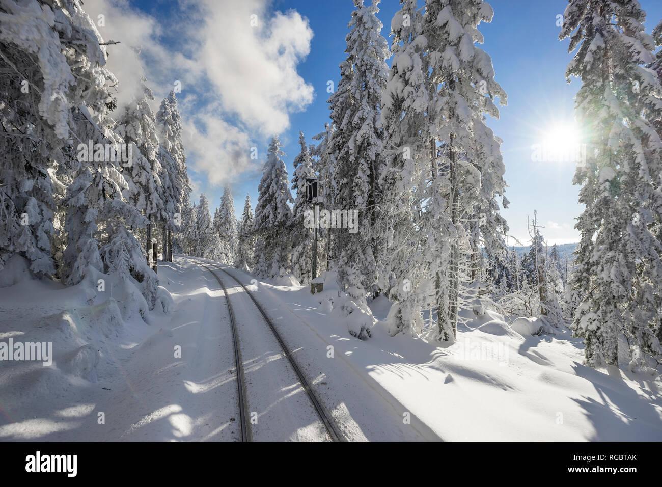 Germany, Saxony-Anhalt, Harz National Park, Brocken, rail tracks of Harz Narrow Gauge Railway in winter against the sun - Stock Image