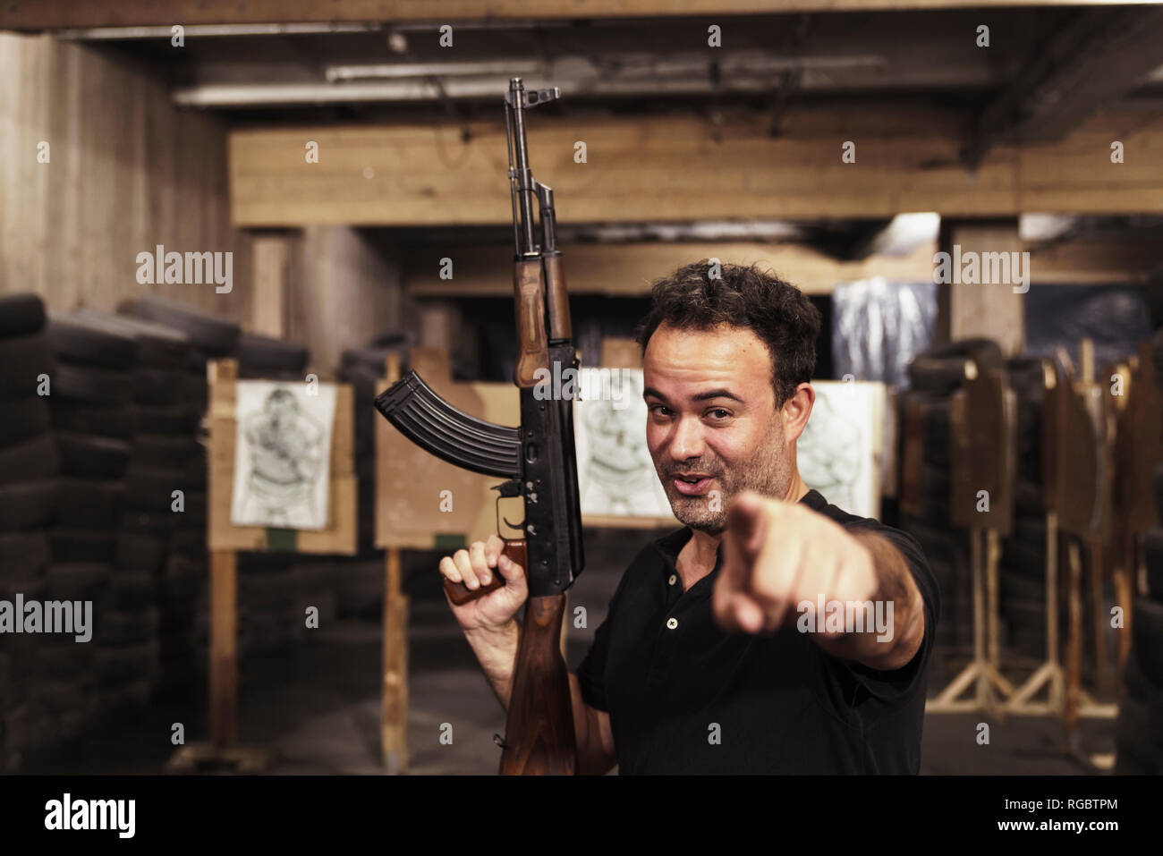 Portrait of man with a rifle pointing his finger in an indoor shooting range - Stock Image
