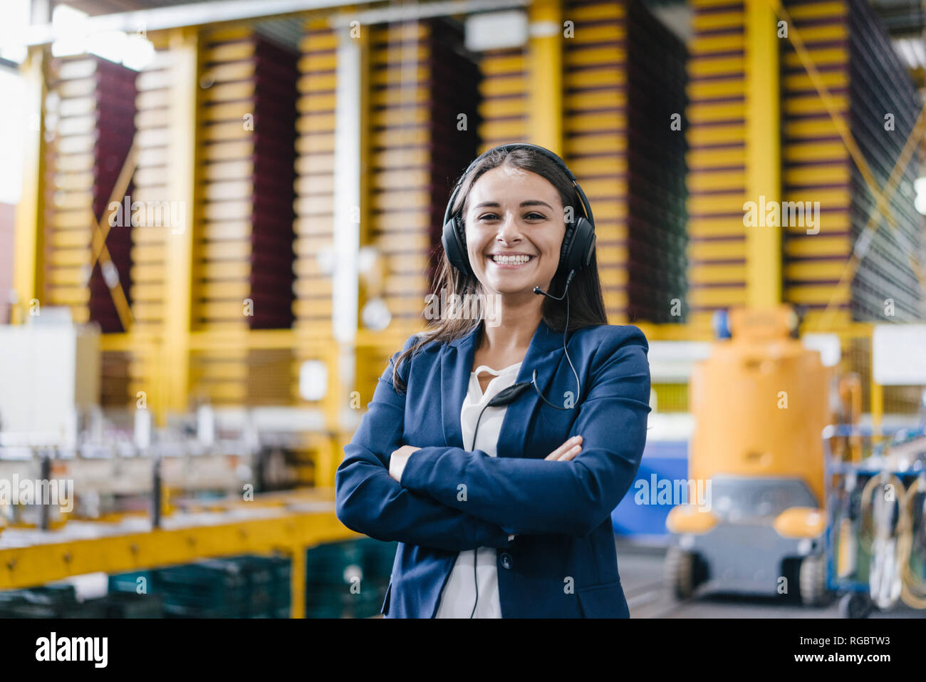 Confident woman standing in logistics center, with arms crossed Stock Photo