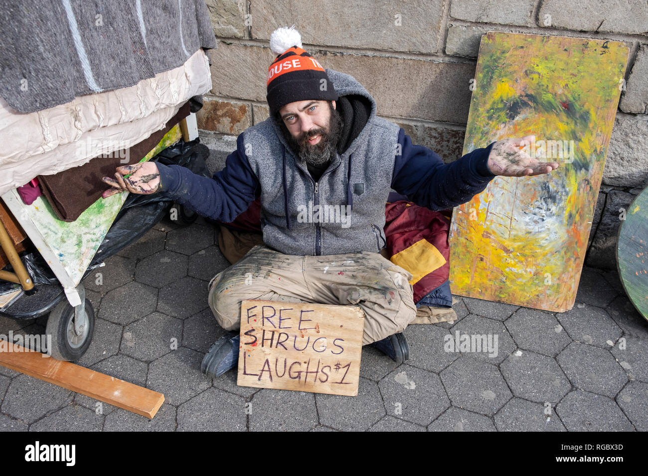 A busker, street performance artist & painter giving free shrugs but selling laughs for $1 each. In Union Square Park in Manhattan, New York City. - Stock Image