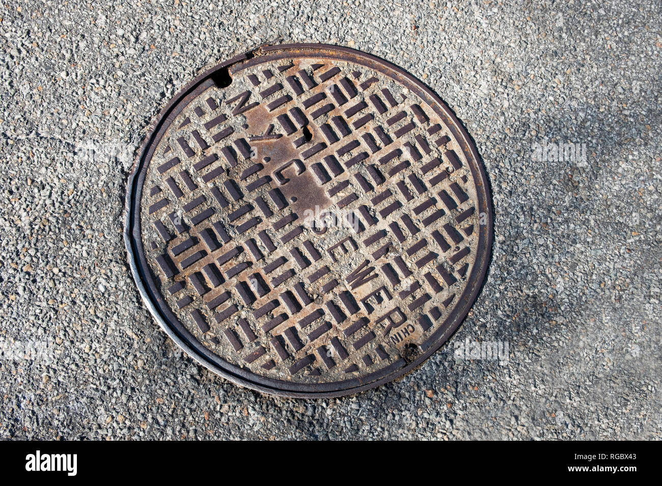A manhole cover in Flushing, Queens, New York that was made in China. - Stock Image