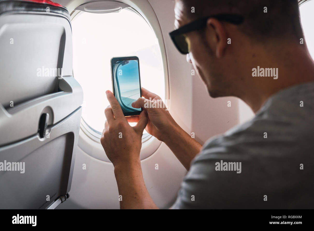 Man in airplane, using smartphone, taking a picture, airplane window - Stock Image