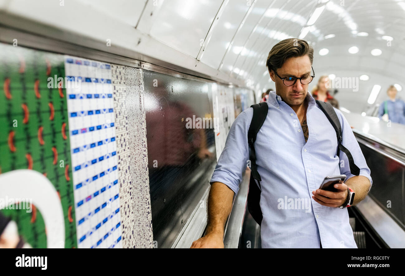 Businessman standing on escalator looking at cell phone - Stock Image