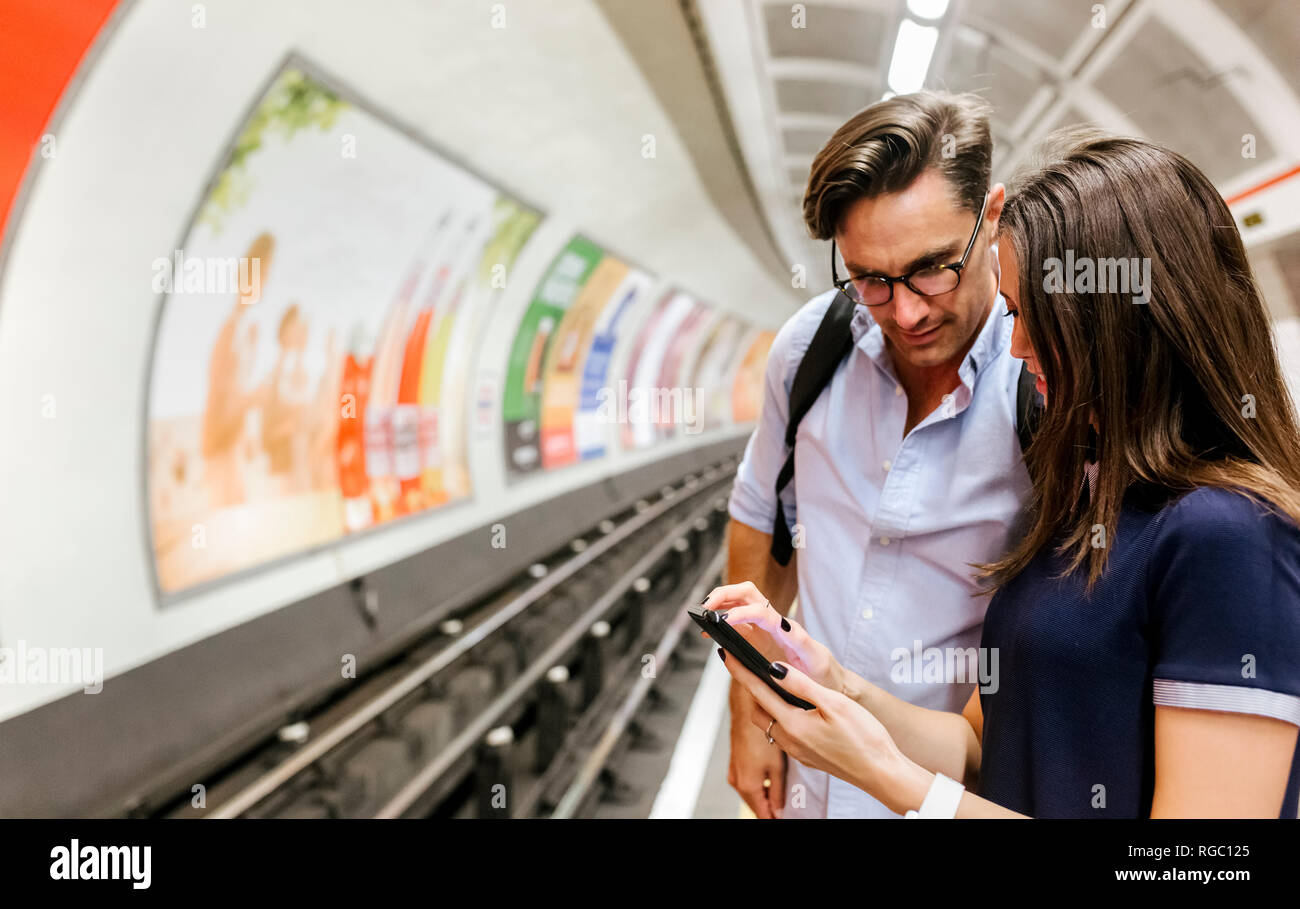 UK, London, young couple standing at underground station platform looking at cell phone - Stock Image
