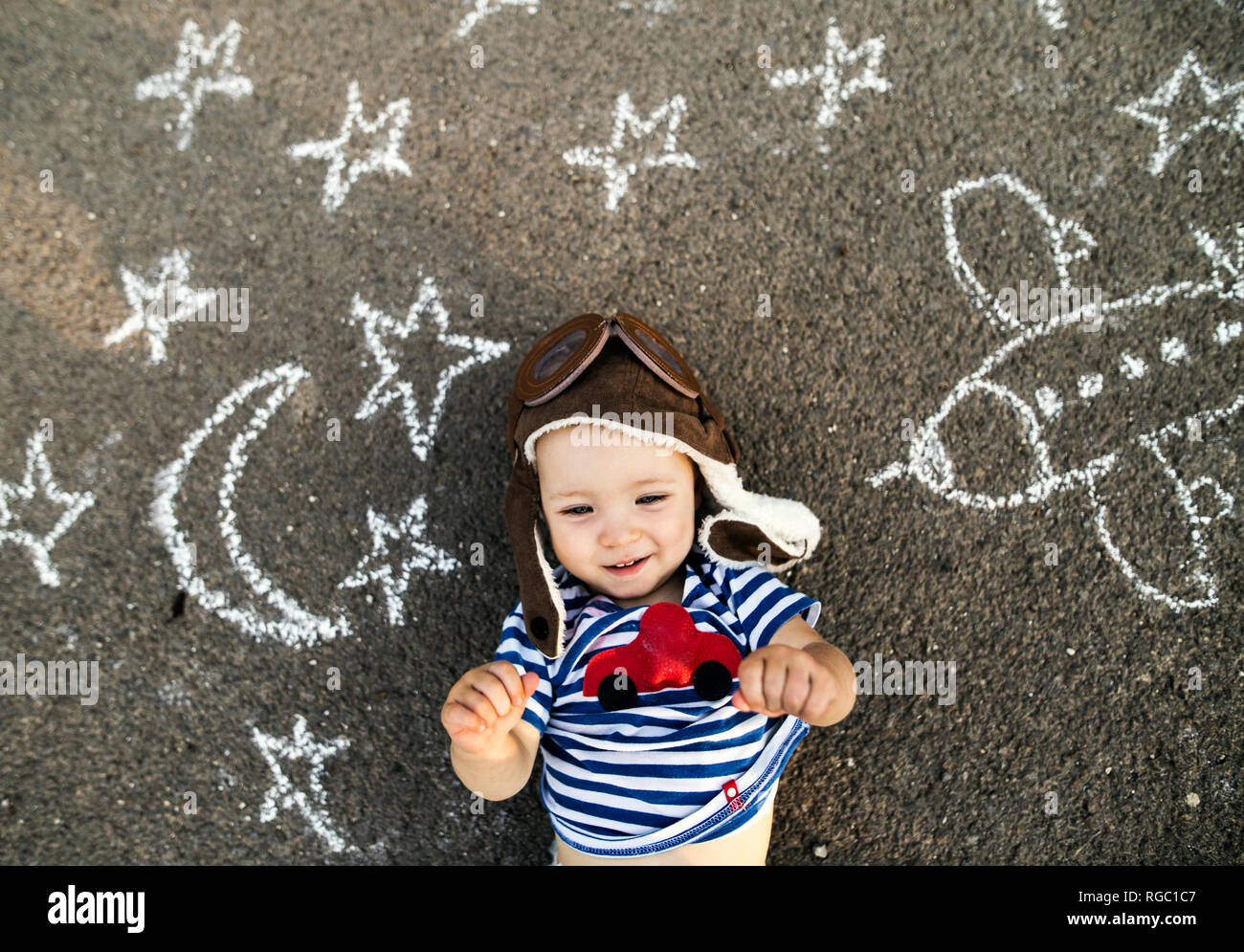 Portrait of smiling baby girl wearing pilot hat lying on asphalt painted with airplane, moon and stars - Stock Image