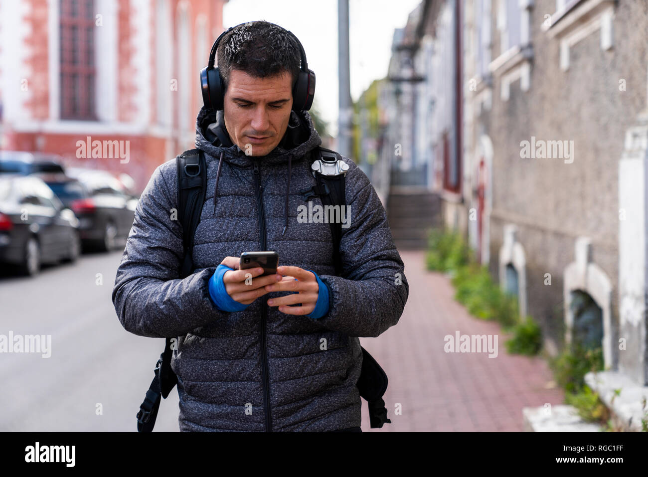 Man in the city on the go with cell phone and headphones - Stock Image