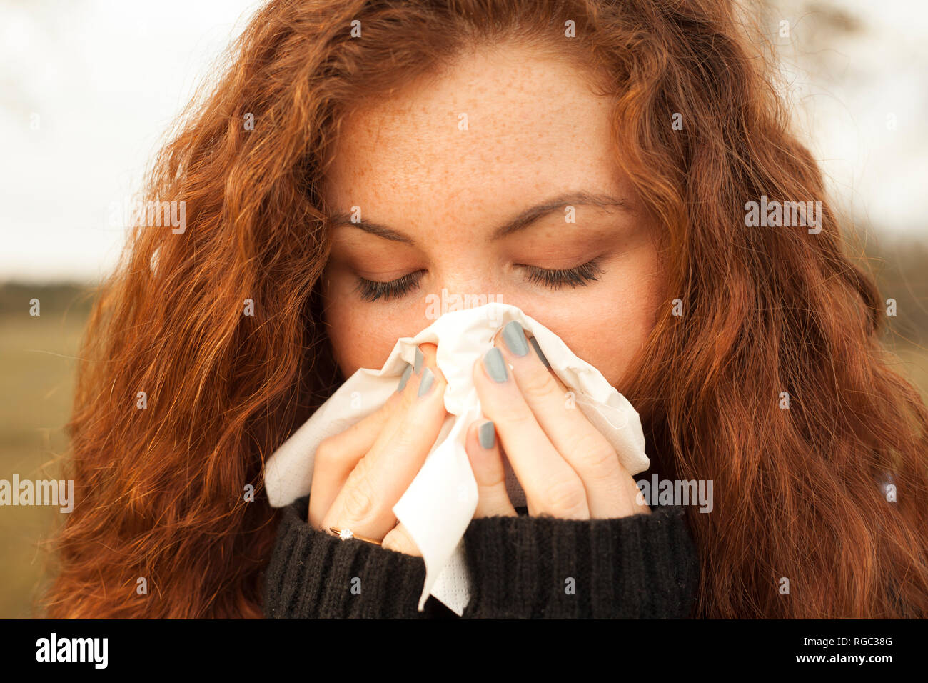 Redheaded young woman blowing nose in nature - Stock Image