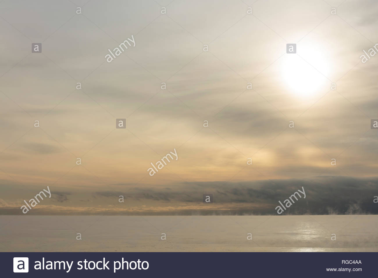 Soft thin transparent overcast cloudy sky diffused winter sun over Lake Ontario in Ontario Canada - Stock Image