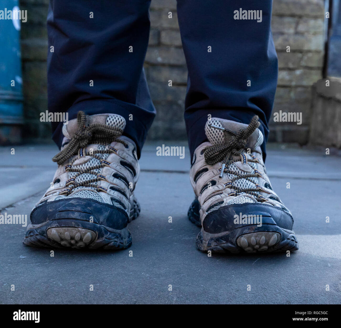 A pair of adult male feet wearing trainers. - Stock Image