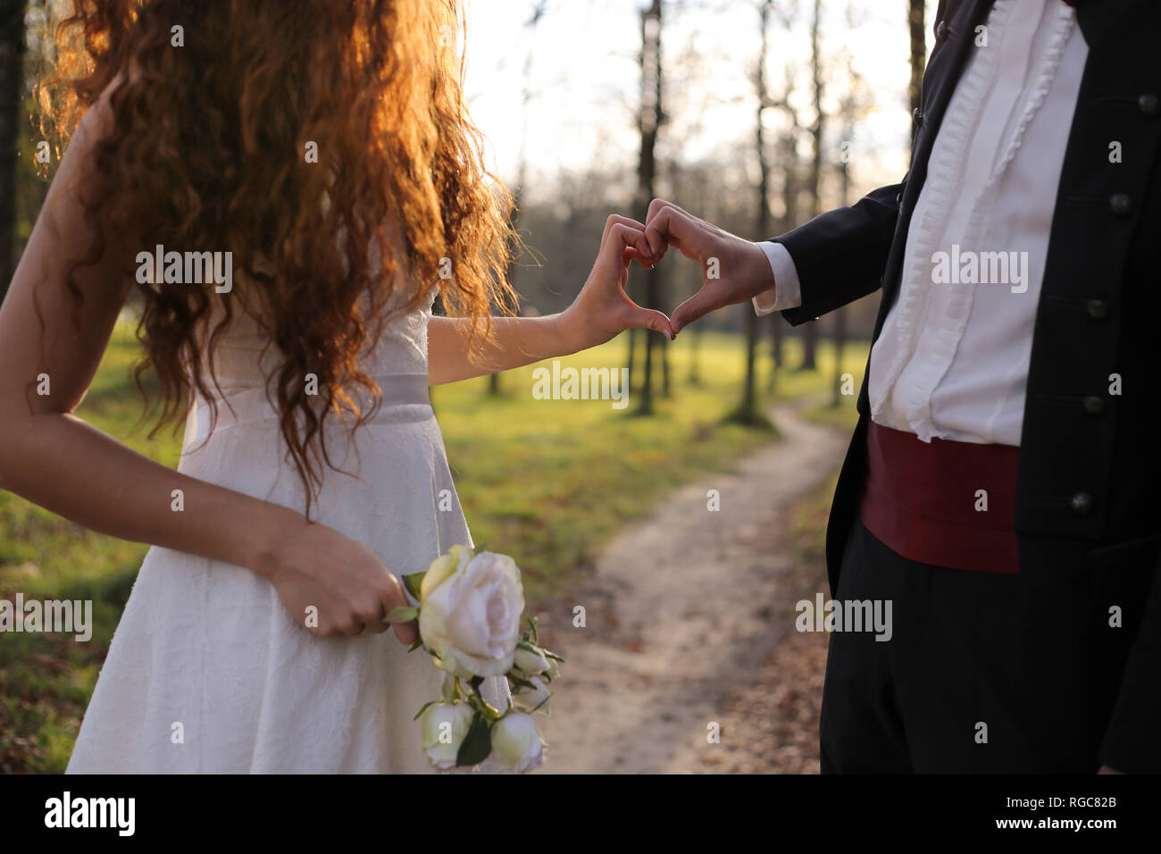 Newly wed bridal couple touching hands, making heart shaped finger frame - Stock Image