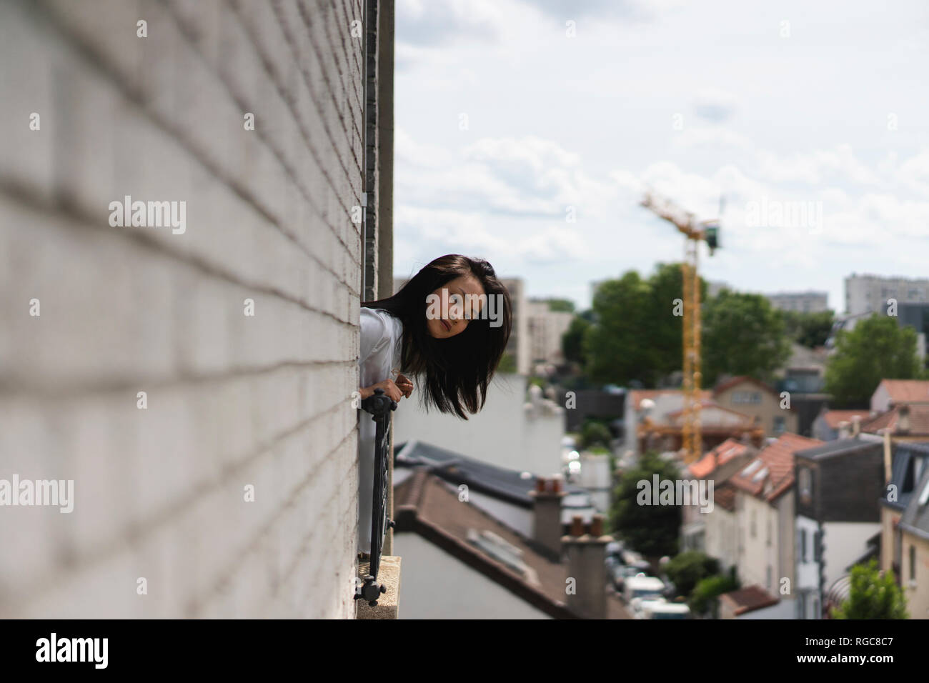 France, Paris, young woman looking out of the window - Stock Image