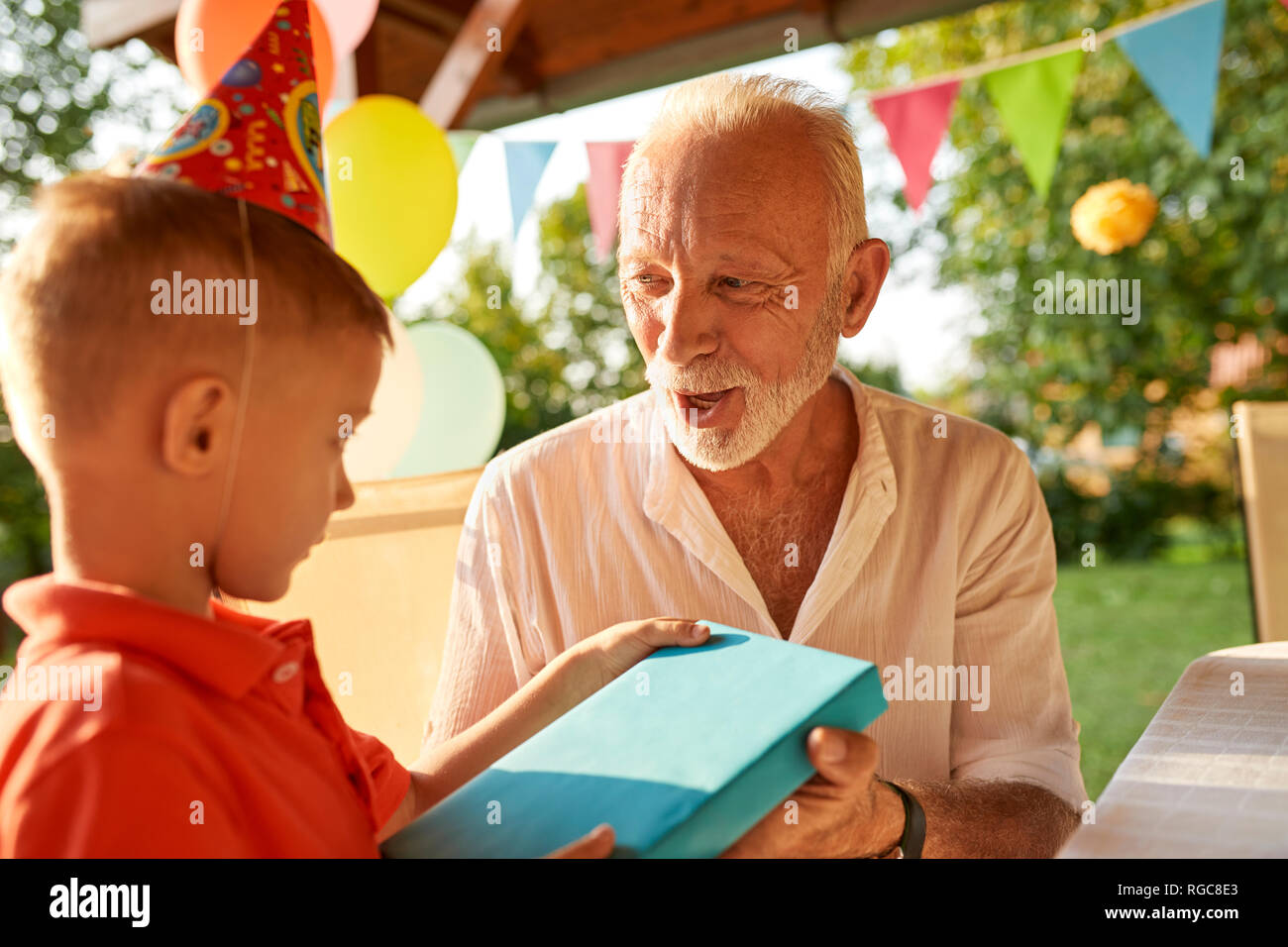 Grandfather handing over present to grandson on a garden birthday party Stock Photo