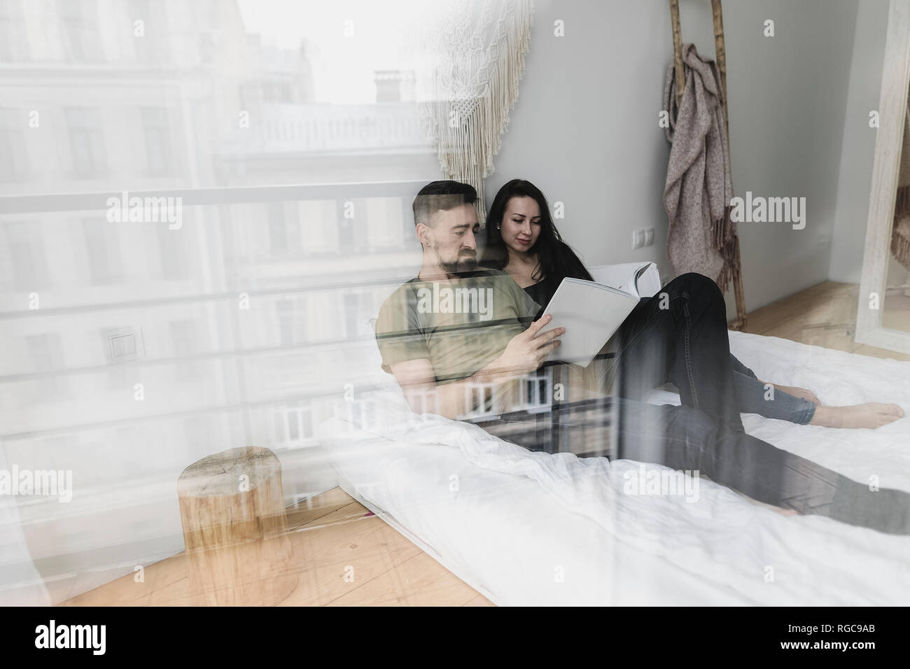 Couple sitting on bed, flipping through a book - Stock Image
