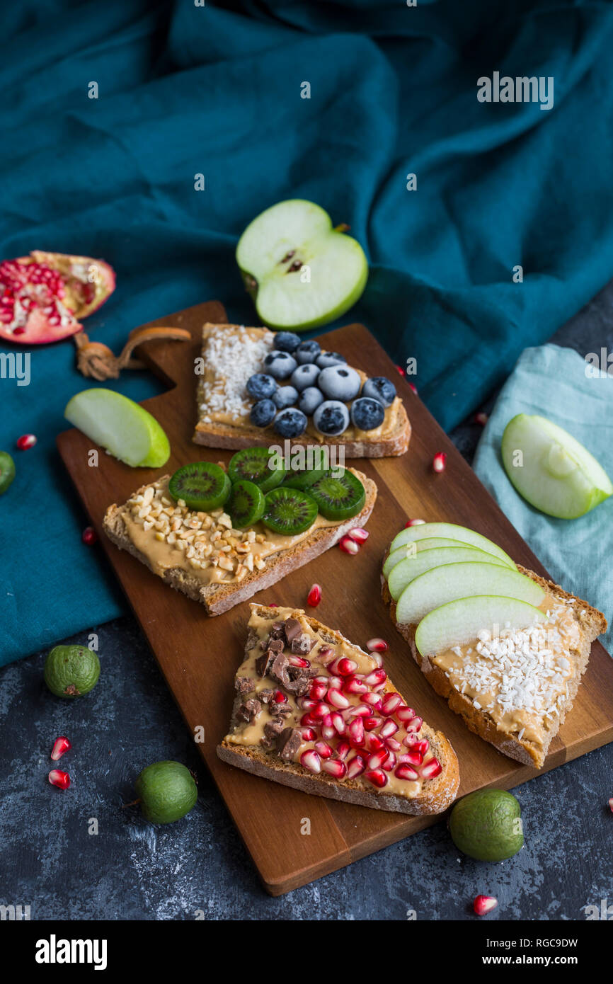 Bread slices with various toppings on wooden board Stock Photo