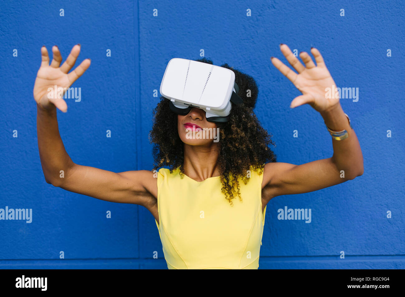 Woman using Virtual Reality Glasses against blue background - Stock Image