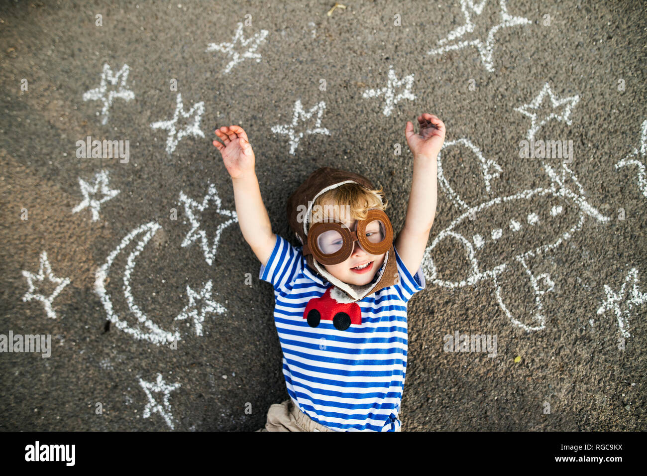Portrait of smiling toddler wearing pilot hat and goggles lying on asphalt painted with airplane, moon and stars - Stock Image