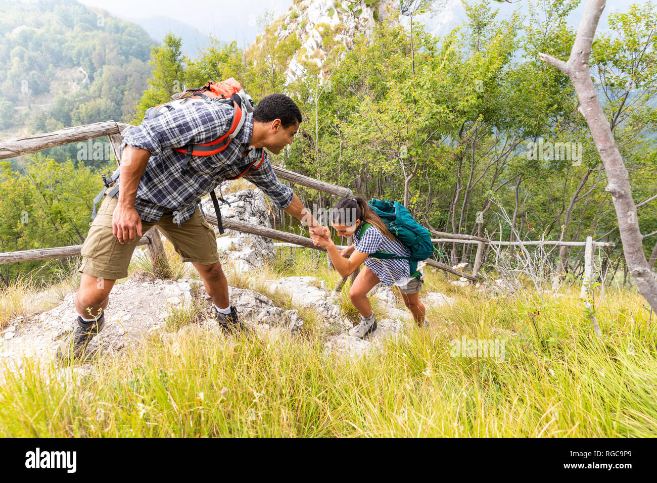 Italy, Massa, man helping a young woman to climb a step while hiking in the Alpi Apuane mountains Stock Photo
