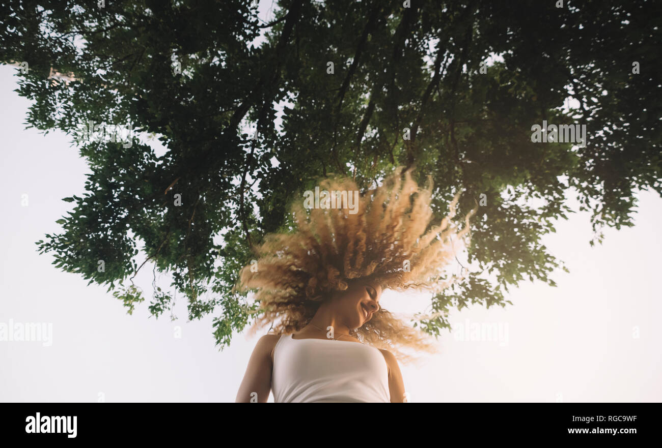 Young woman with blond ringlets tossing her hair Stock Photo