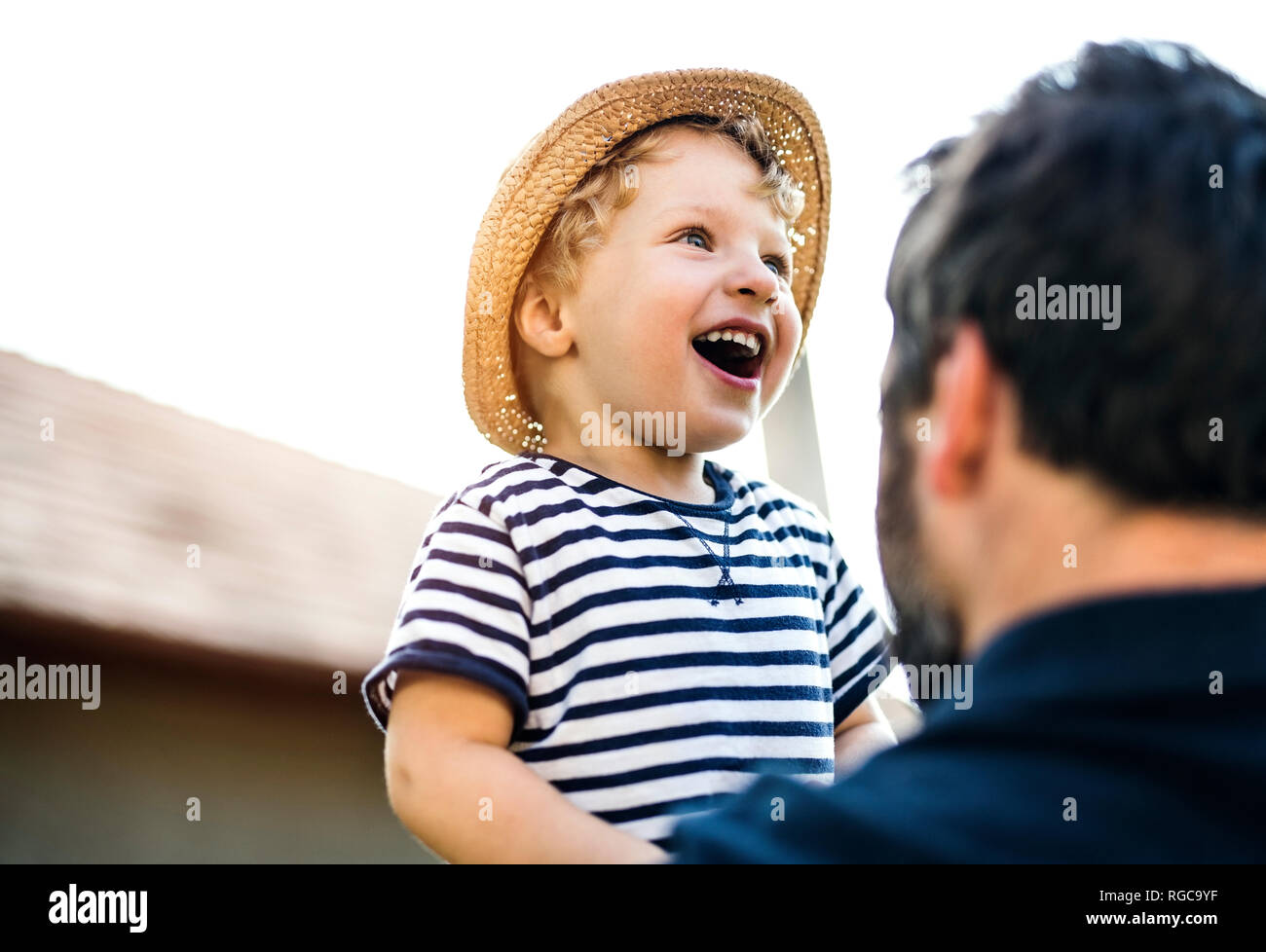 Portrait of laughing toddler on his father's arms - Stock Image