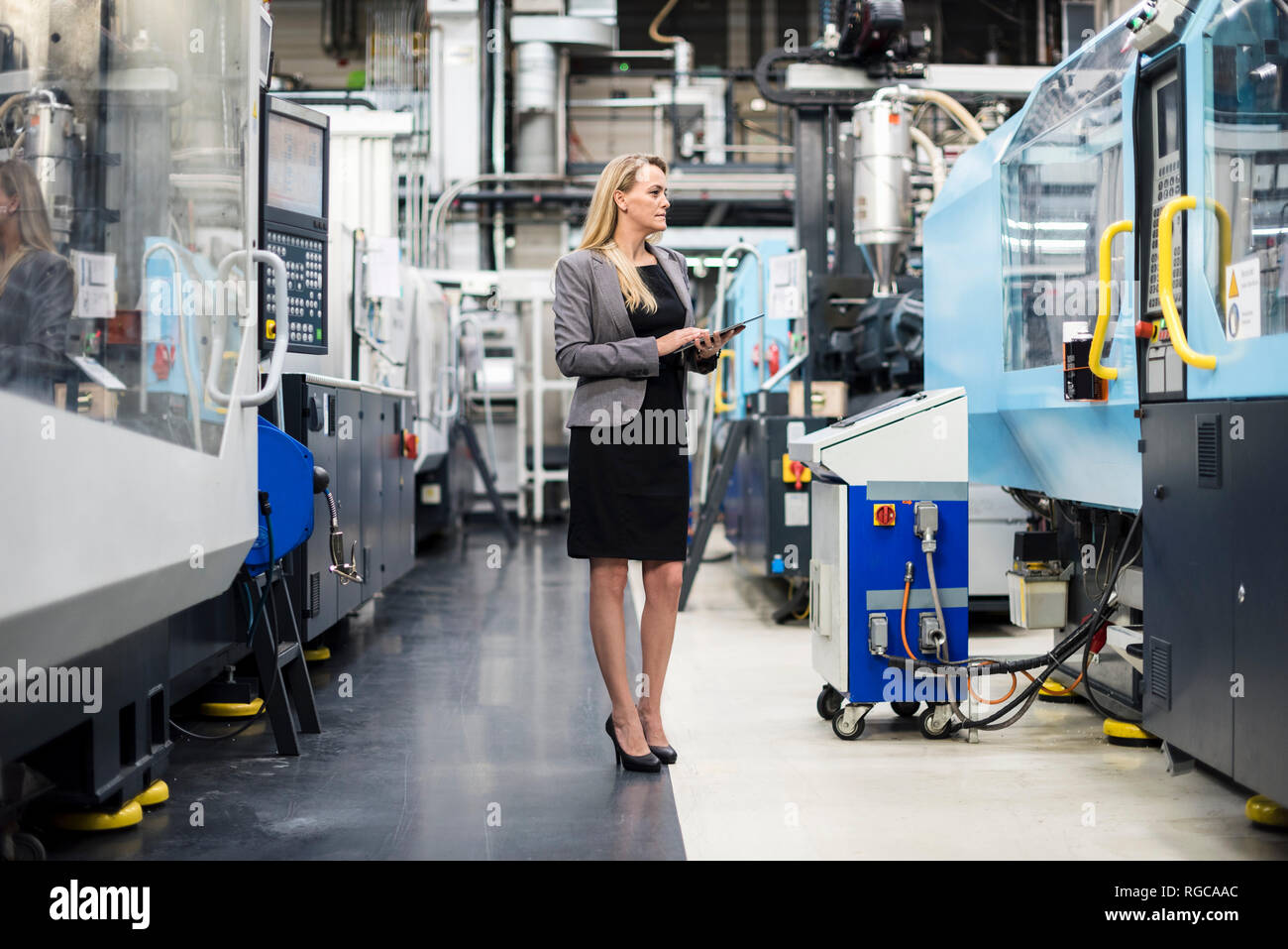 Woman using tablet at machine in factory shop floor Stock Photo