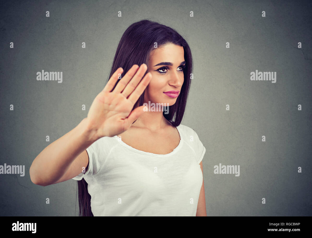 Portrait of an angry woman with bad attitude giving talk to hand gesture with palm outward isolated on gray background. Negative emotion face expressi - Stock Image