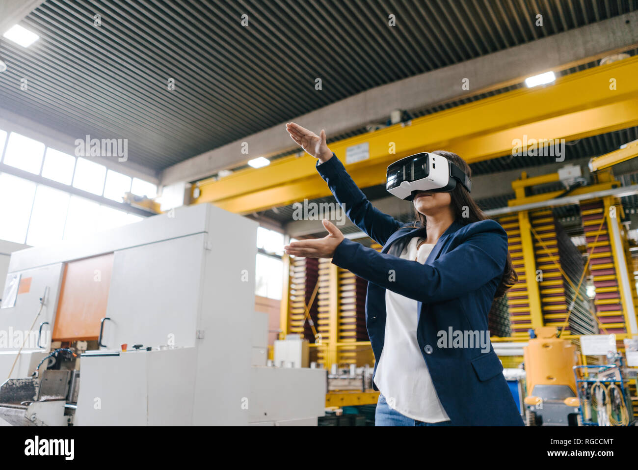 Young woman working in distribution warehouse, wearing VR