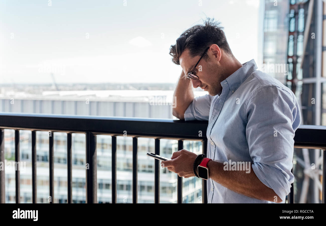 UK, London, man using cell phone on a roof terrace - Stock Image