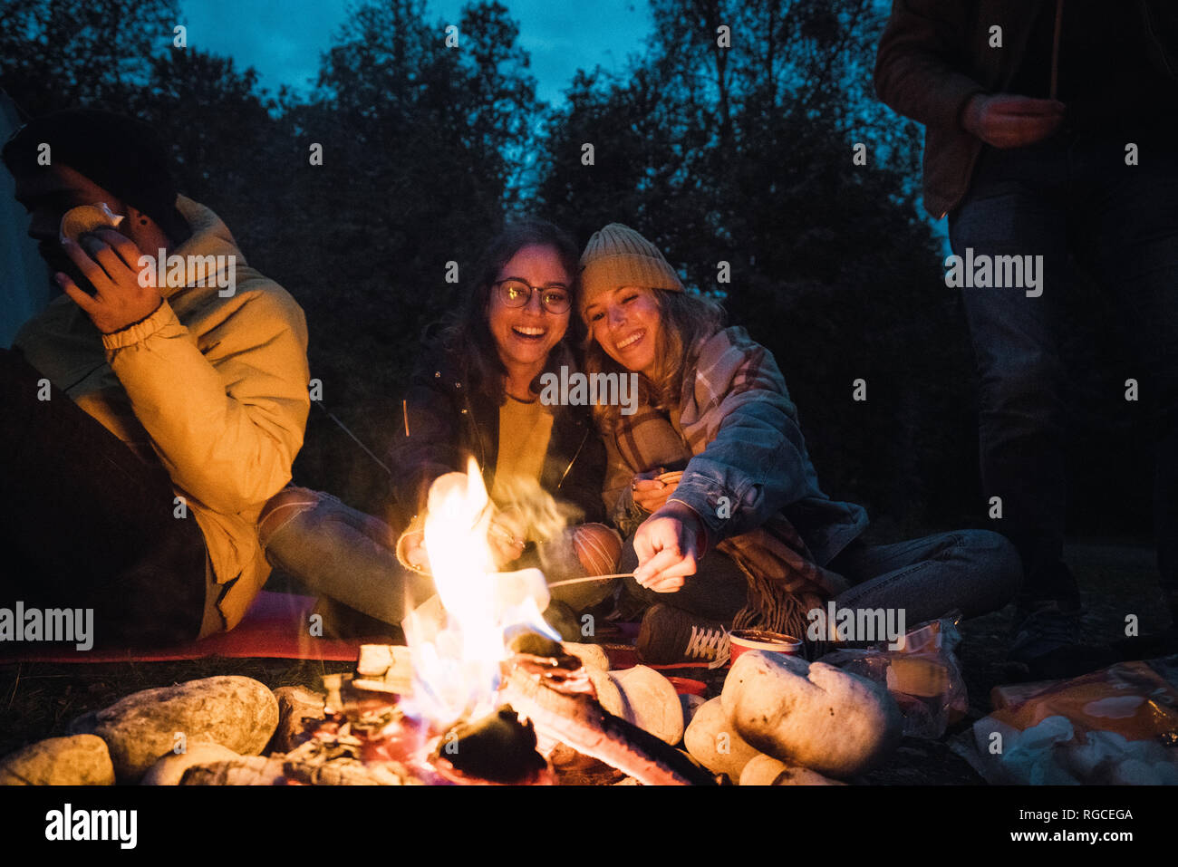 Group of friends sitting at a campfire, roasting marshmallows - Stock Image