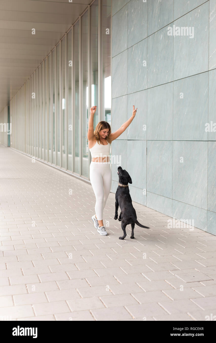 Smiling young woman dressed in white sportswear playing with her dog Stock Photo