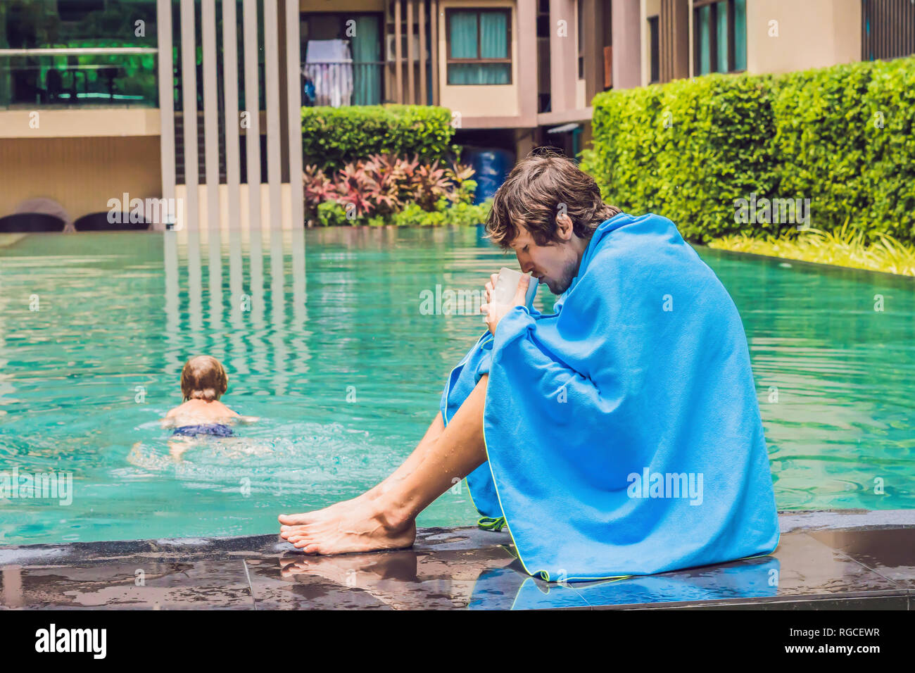 Sick man traveler. The man caught a cold on vacation, sits sad at the pool drinking tea and blows his nose into a napkin - Stock Image