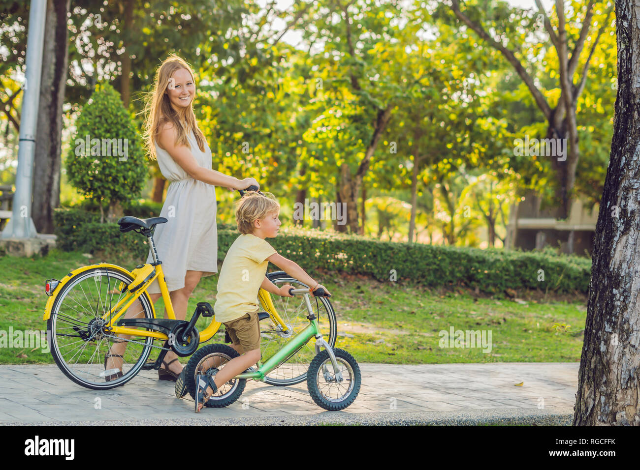 Happy family is riding bikes outdoors and smiling. Mom on a bike and son on a balancebike Stock Photo